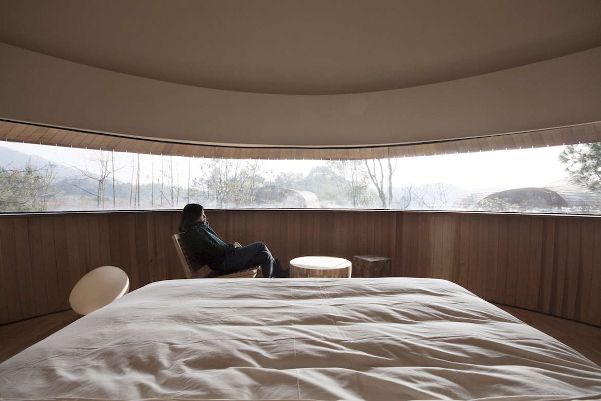 A person sits looking out the curved windown inside The Mushroom by ZJJZ