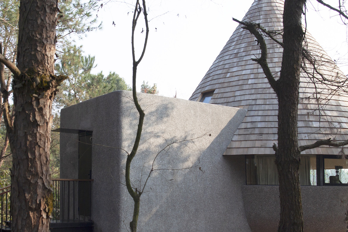 Exterior view of the shingled roof and grey cement wall of The Mushroom by ZJJZ
