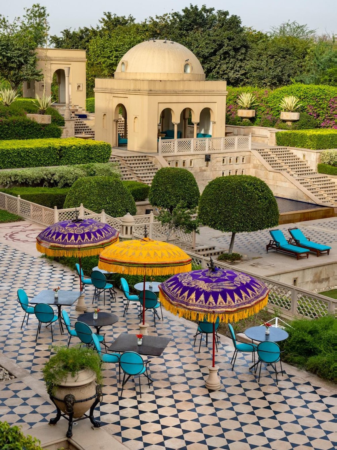 Colourful umbrellas and blue seats line the terrace at Bellevue at The Oberoi.