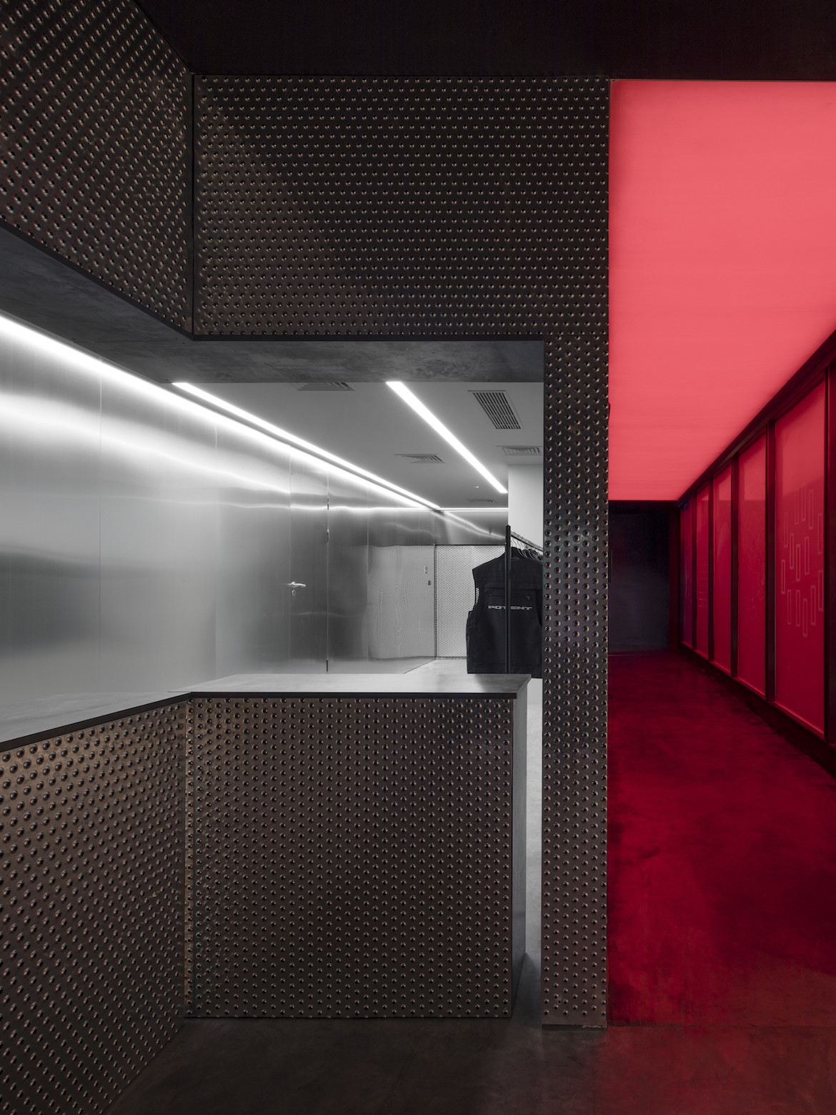 Perforated metal lines the cloakroom which is next to a red corridor leading into the club.