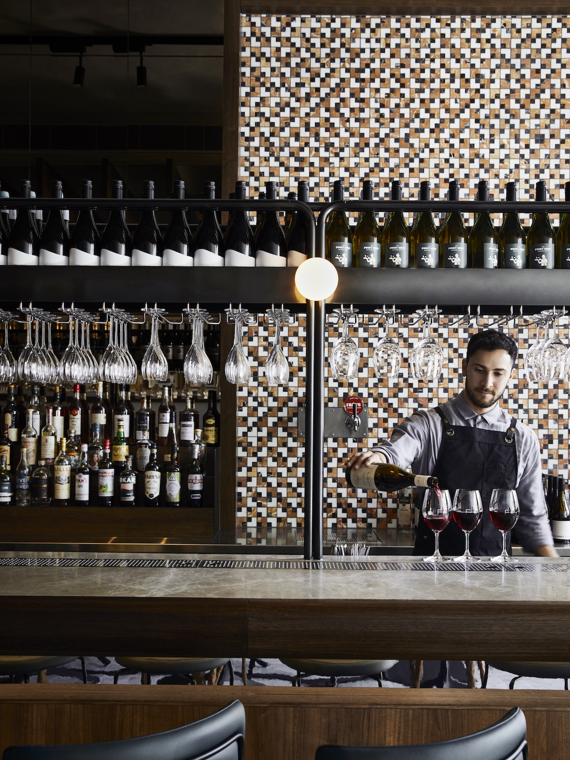 A bartender stands in front of a tiled wall in Frederic Bistro by Léo Terrando