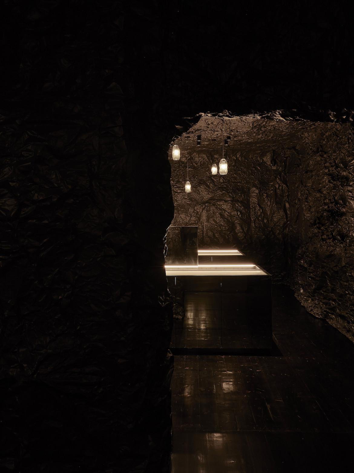 A dark cave-like hallway with black rippling walls leading to Sarah & Sebastian jewellery displays.