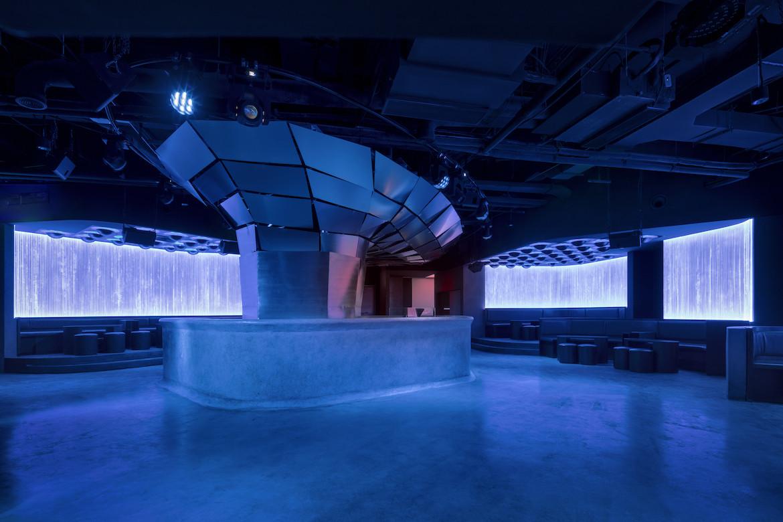 A sculptural bar inside Potent club under blue lights.