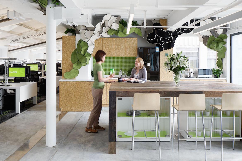 Two women talk in the green, tan and white Glumac Shanghai office.