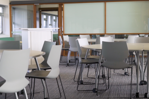 A room feautring Buro's white ergonomic Konfurb Fly Sled Chairs around circular tables.
