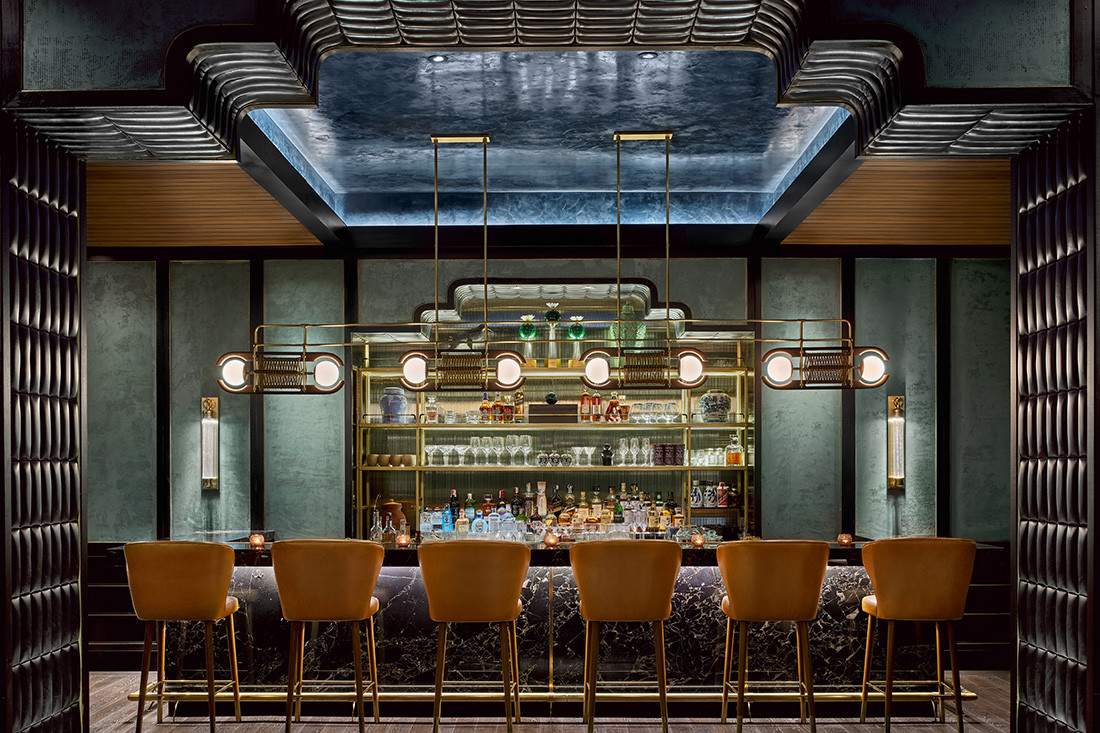 Chinese-inspired portals separate the bar, bar/dining and main dining spaces at Nan Bei by AvroKO, Bespoke textured green plaster on the walls and lapis lazuli stone on the bar play off against warmer tones.