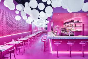 The pink interior of Ping Pong, with a bar lined with pink powder-coated derlot stools and tables lining the other wall.