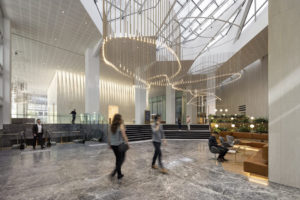 People walk underneath the sculptural hanging lighting in the lobby of 600 Bourke Place.