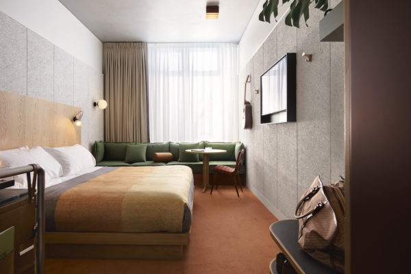 A bed and ochre and eucalyptus furnishings by David Flack in Ace Hotel