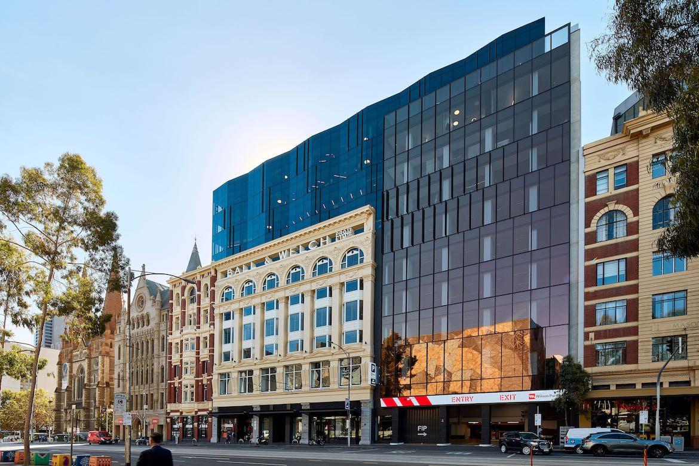 Black glass and historic yellow exterior of Hub Flinders Street.