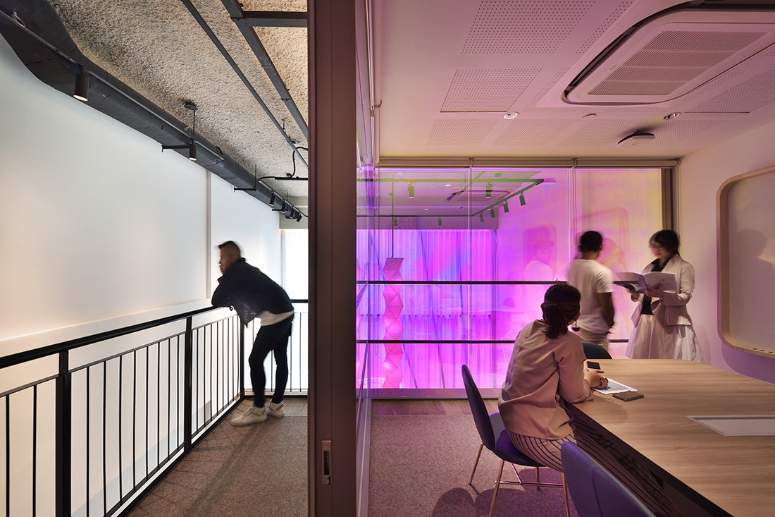 Dichronic lighting sets a futuristic feel in the co-working space.