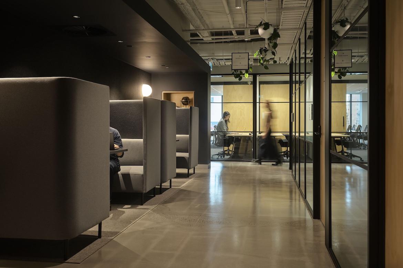 People sit in quiet grey working pods in Hub Flinders Street