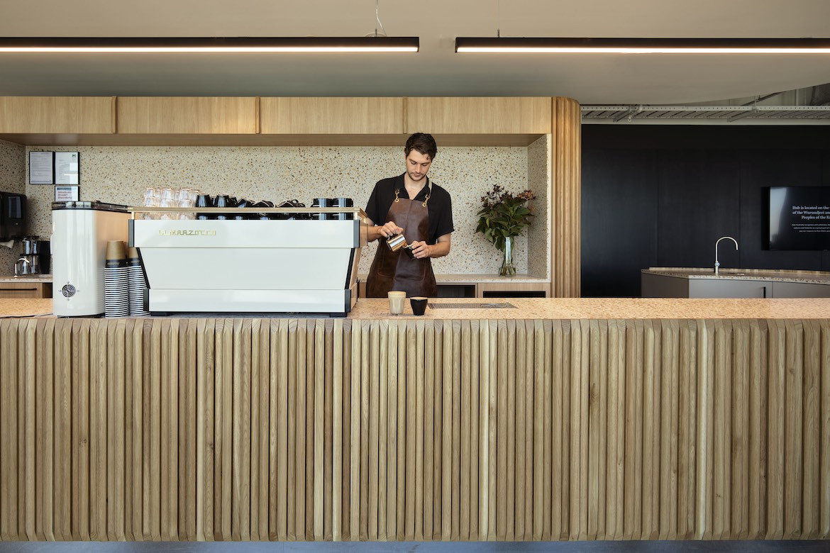 A barista pours a coffee behind the panelled cafe bar.