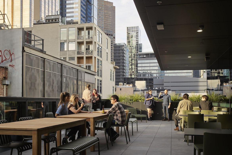 People talk to each other on the Hub Flinders Street terrace.