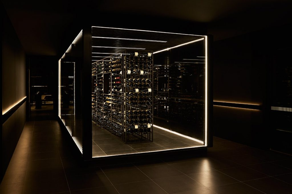 The dramatically backlit fine wine display at the reception and concierge point.
