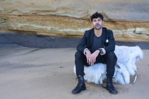 Léo Terrando sits in front of a rock wall on a beach.