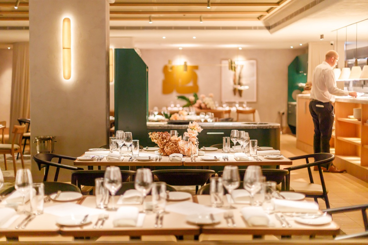 Set tables inside Neil Perry's Maragret, with pops of green and glowing wall sconces in the background.