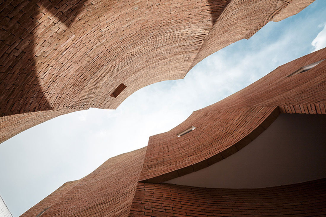 Brick walls with multiple curvatures frame the sky at Sala Ayutthaya. The shadows change constantly throughout the day. Photo by Wison Tungthunya.