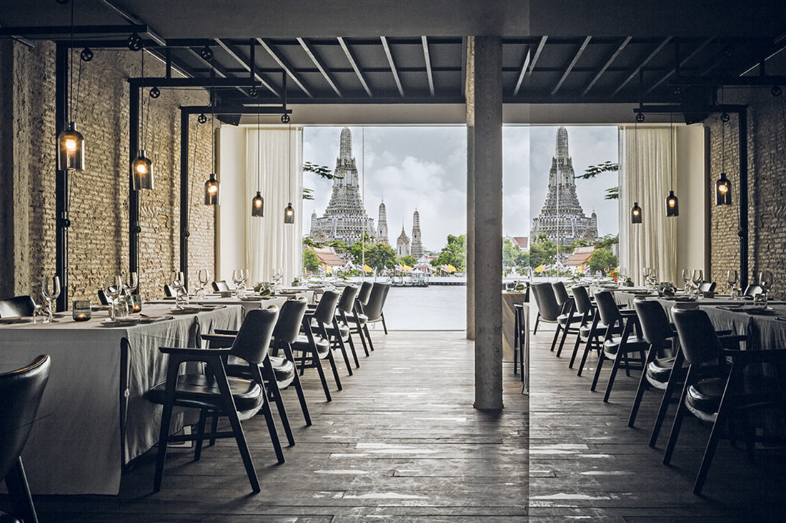 A mirrored wall within the restaurant at Sala Rattanakosin reflects the Temple of Dawn across the Chao Phraya River. Photo by Wison Tungthunya.