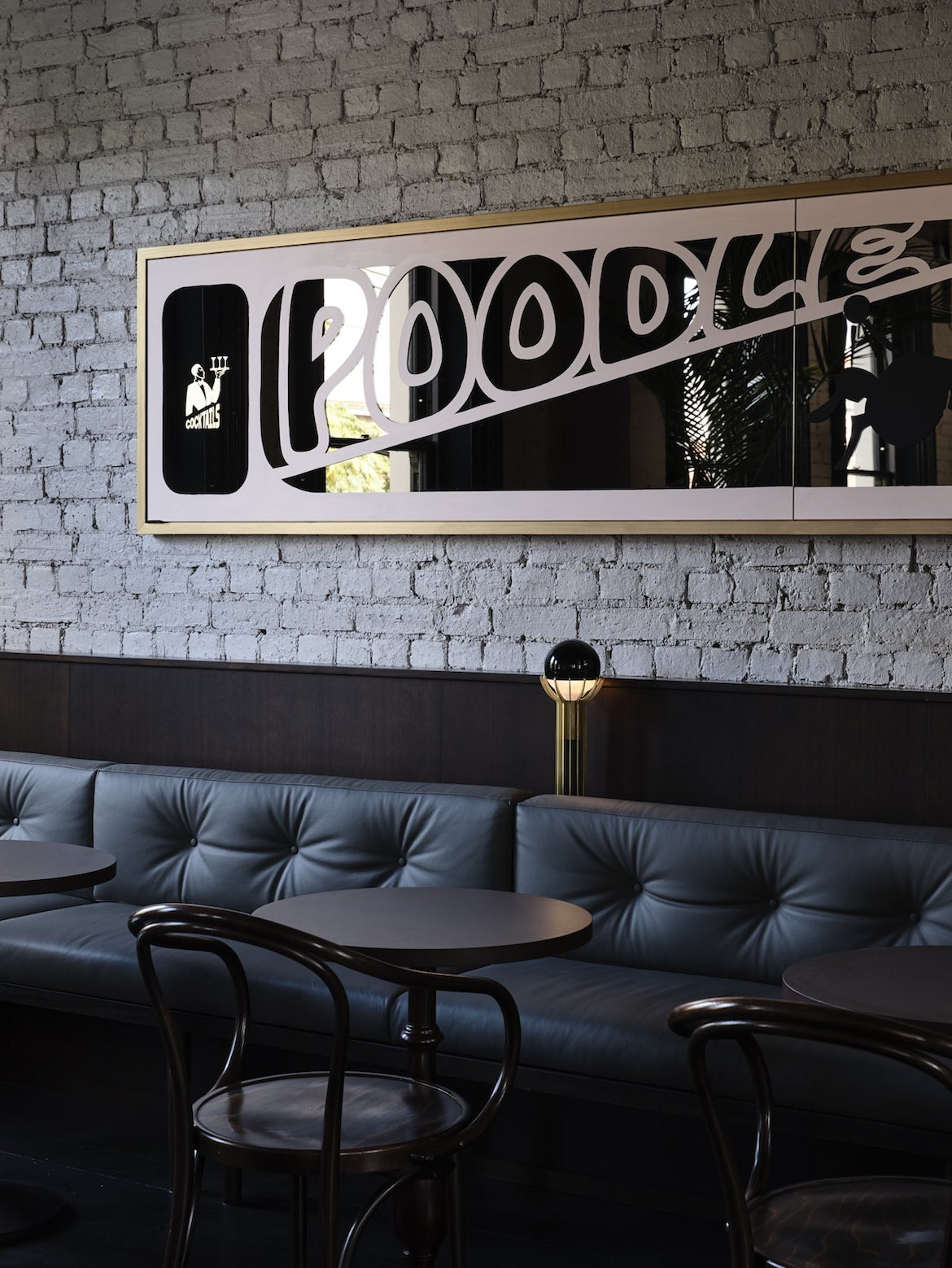 A mirrored sign reads 'poodle' above a row of couches in Das Studio's Poodle projec.