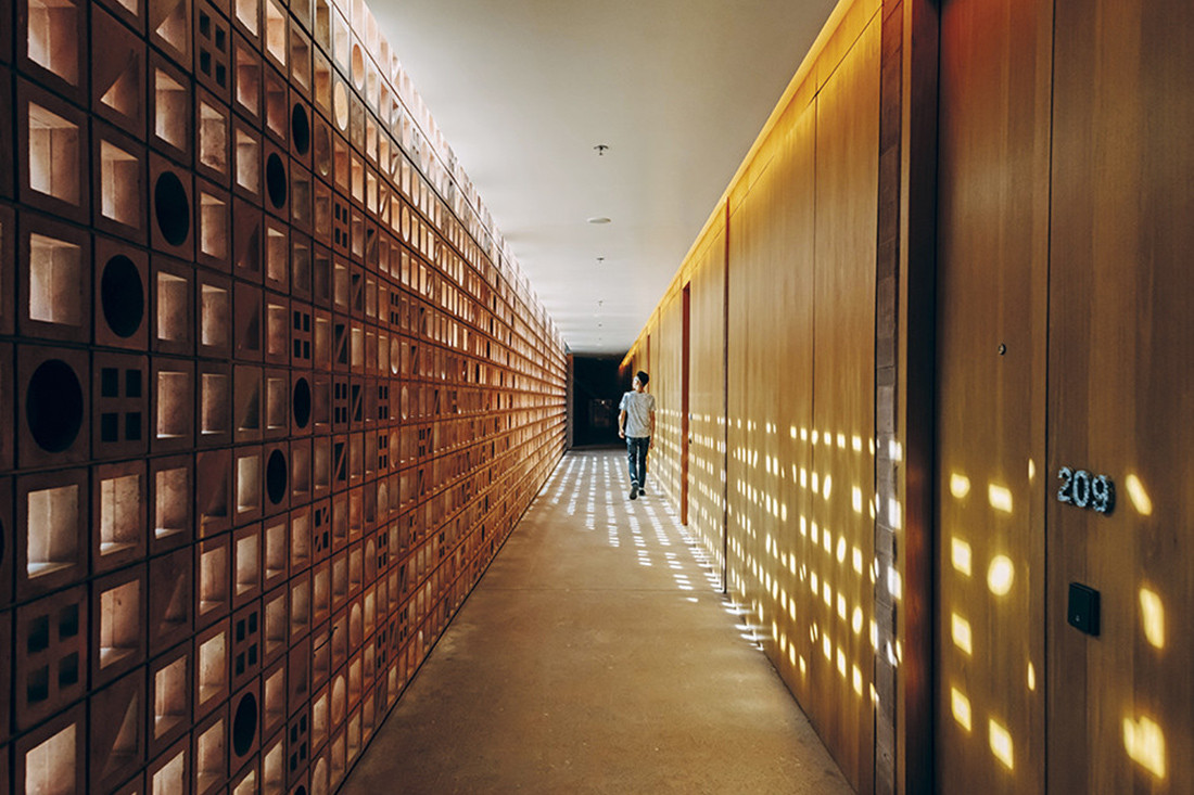 Handcrafted breeze blocks lend a unique pattern of light and shadow to a corridor at Potato Head Studios.
