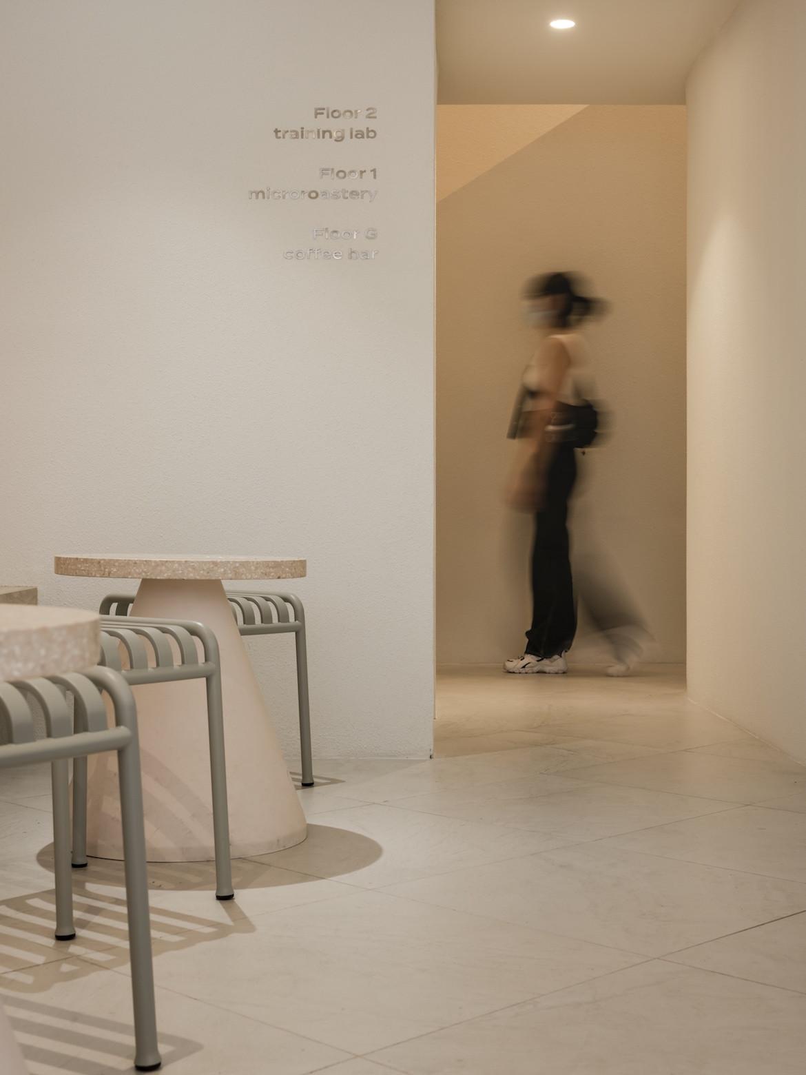 A person walks through a doorway in Exterior of PAGA Microroastery.