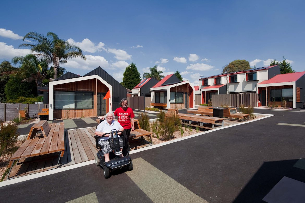 A man in a red shirt stands next to a lady in a mobility scooter at Bent's Dandenong public housing.