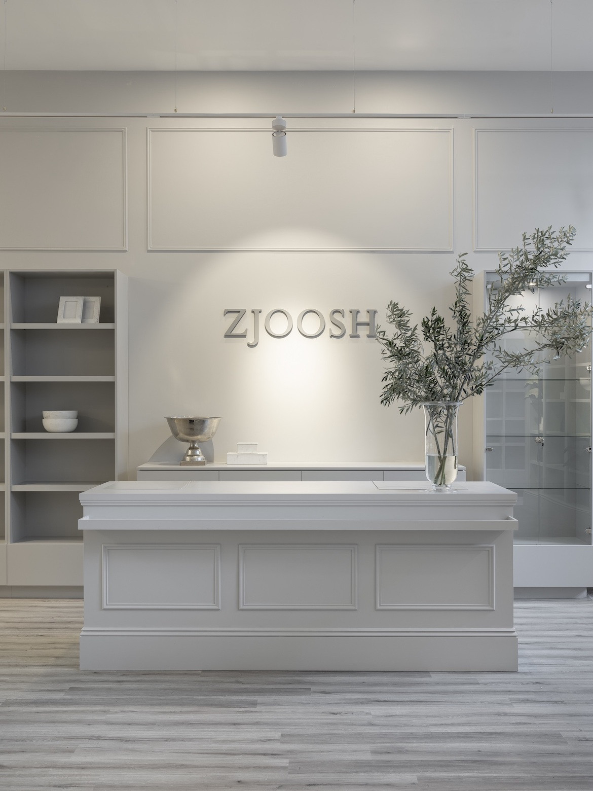 A counter with a white top in front of Dior-grey walls that have the Zjoosh logo.