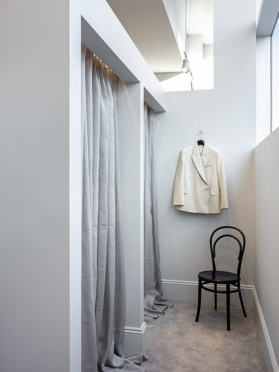 A changeroom with grey curtains, grey cashmere carpets, a black chair and a jacket hanging on the wall.
