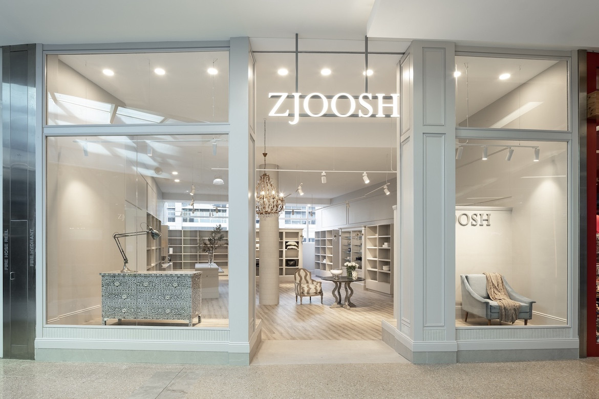 The exterior of the store with large windows and an illuminated Zjoosh sign.