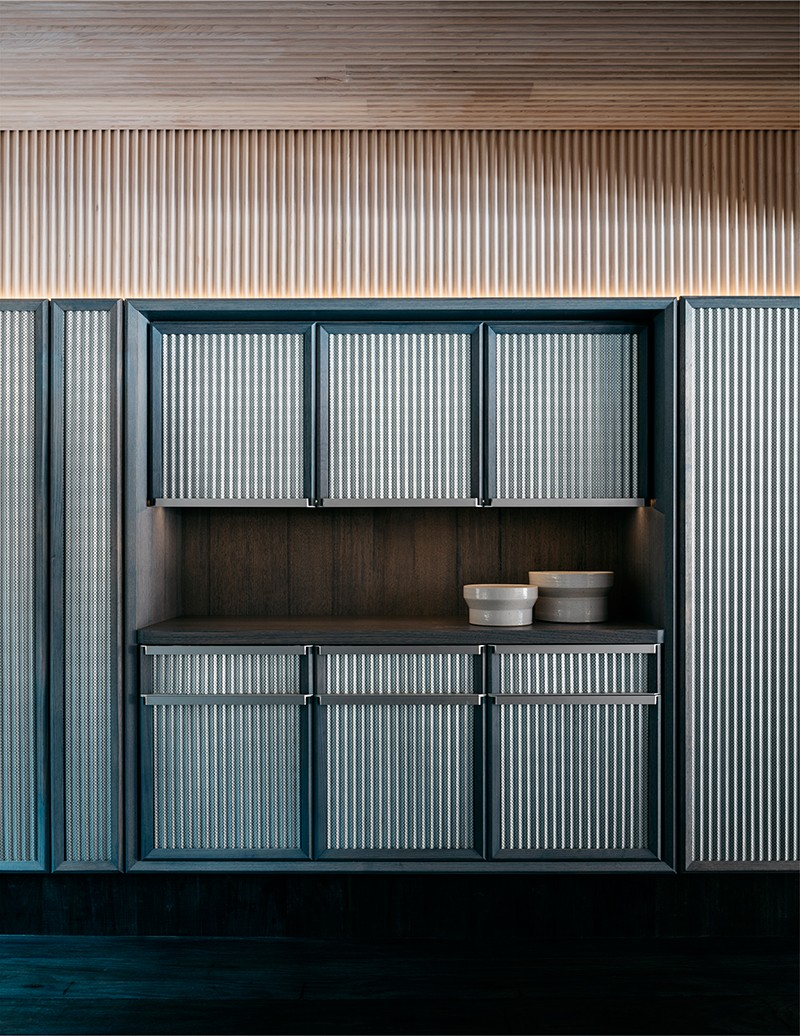 A corrugated Mini Orb material has been applied all throughout the interior, including the waiter station.