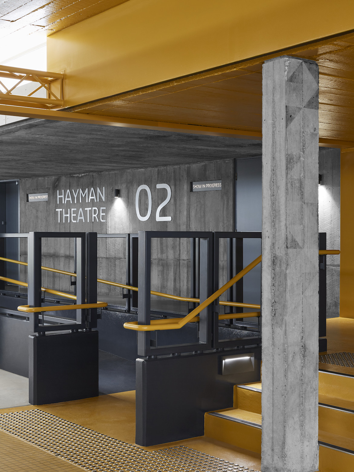 Yellow roof, flooring and accents on a grey background of the Hayman Theatre.