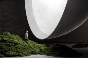 A man in a white shirt stands among moss-covered rocks looking into the large white Hometown Moon shape