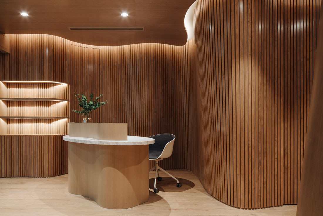 The flooring is vinyl in a similar light brown tone and shelving cushioned benches and the reception desk follow the same organic language to blur the
