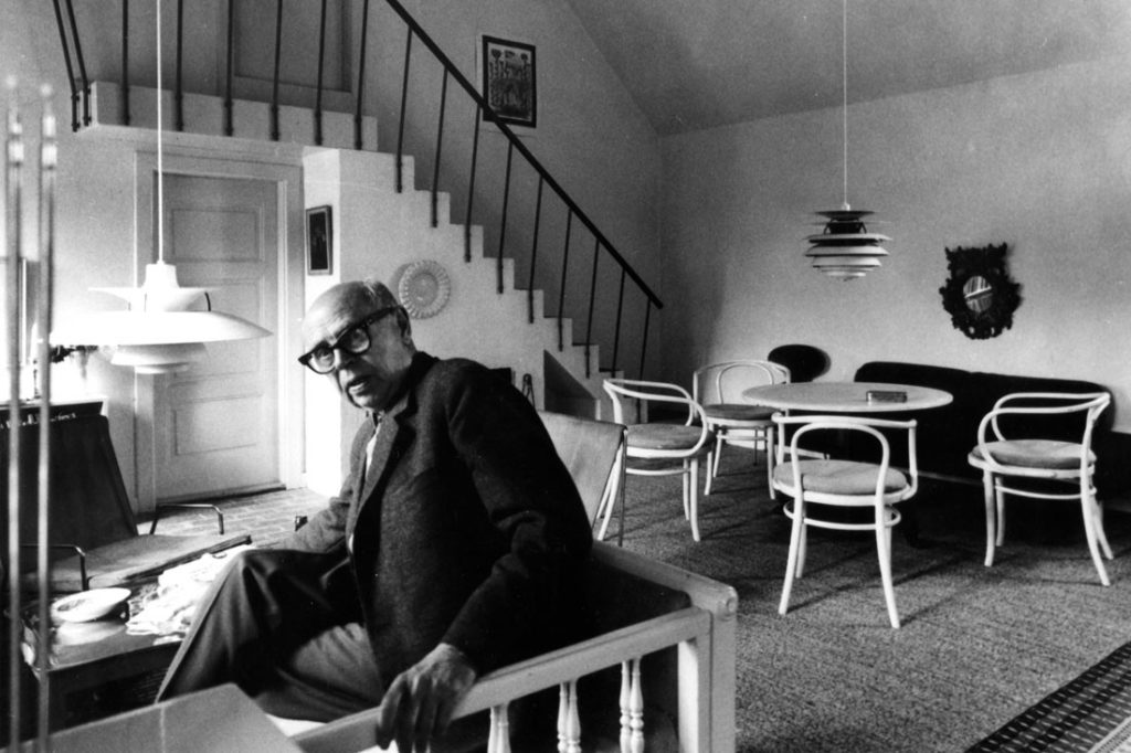 Poul Henningsen in his home in Hørsholm, Denmark with his iconic PH 5 and the Contrast pendant in the background. Image courtesy of Louis Poulsen